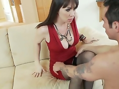 Hot and breasty black haired milf in sexy red dress RayVeness gets her shaved taco licked on the couch in her living room by a excited young black haired dude Joey Brass and enjoys